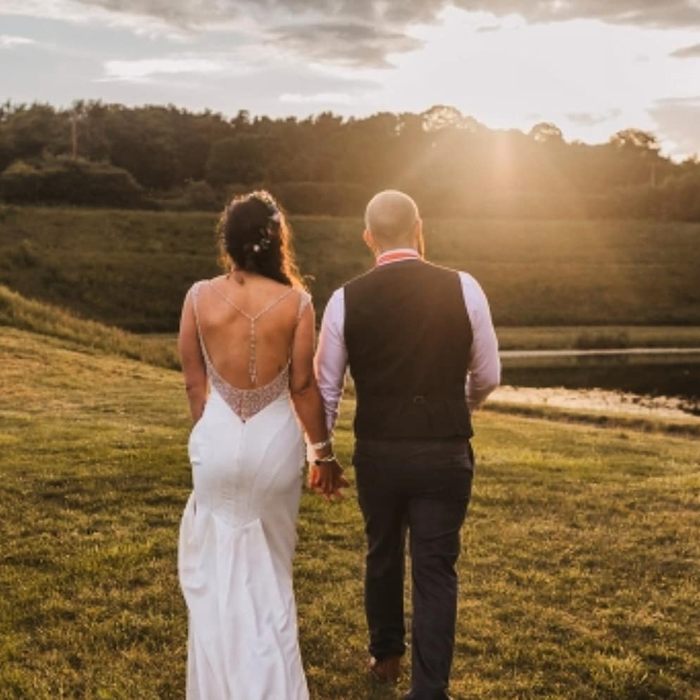 A bride in her altered wedding dress with her husband looking into the sunset