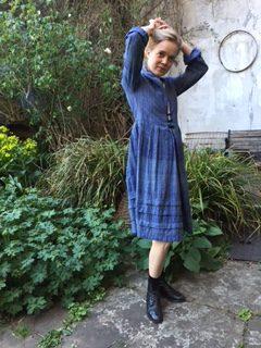 A girl wearing a bespoke coat dress in blue in a garden setting